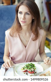 Portret of attractive young woman in a pink dress has lunch in a restaurant. A dish with salad and drinks on the table.