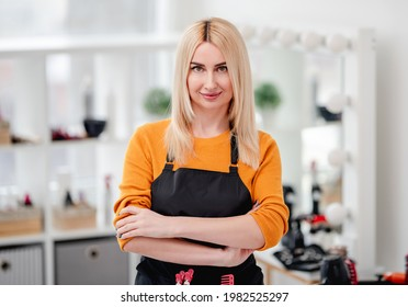 Portret of beautiful blond hairdresser woman staying in salon and holding hands crossed - Shutterstock ID 1982525297