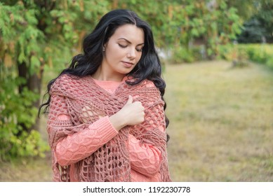 Portret of the beautiful long-haired brunette girl, looking down, in the cold autumn day she wraps herself in an openwork shawl