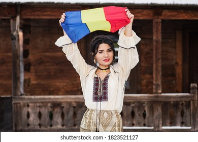 Portret of a beautiful young woman posing in romanian traditional costume in the village museum in winter with the Romanian flag in her hand. - Shutterstock ID 1823521127