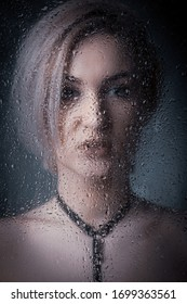 Portret of a blonde girl behind wet glass against a dark background.