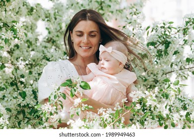 Portret cute beautiful young happy mom in a white shirt is holding her six month old daughter in a pink dress. Happy motherhood and happy childhood. Photo of a blooming apple tree background. - Shutterstock ID 1989949463
