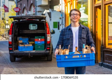Portret of a happy smiling young entrepreneur delivering wine and food by a local restaurant. With his black transporter car in the background