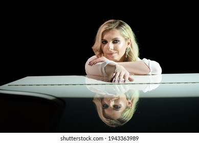 Portret of pianist posing near white piano on the stage in the beam of light. - Shutterstock ID 1943363989