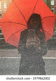 a portret with a red umbrella with white dots, reflected in a window of a shop