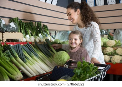 portret of young woman with beautiful daughter choosing green vegetables at store