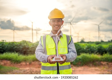 portriat of asian engineer male hand holding the wind turbine model and smiling with the background of wind turbine farm. Environmental friendly. Renewable energy technology and sustainability.