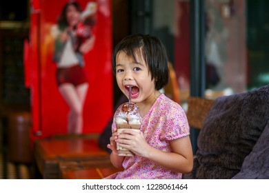 Portriat Asian little girl drinking blended ice chocolate with funny face. Happy girl enjoy eating soft drink with big smile and dimples on cheek at the cafe