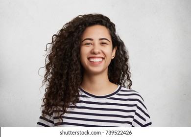 Portriat of pretty curly female wears striped black and whitte t shirt, smiles happily as being glad to meet best friend, who tels her funny jokes or stories. Happiness and facial expressions concept