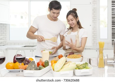a portrit of yong asian couple , a beautiful asin woman show a menu in taplet to lively for cooking dinner, Concept couple in kitchen.