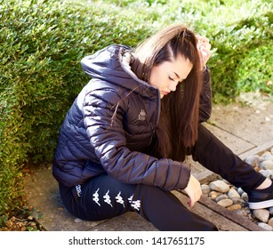 Portsmouth. Portsmouth City. United Kingdom. 7th November 2016. A young beautiful female sitting down with her dark blue Kappa coat, tracksuit bottoms and trainers on, on a sunny day.