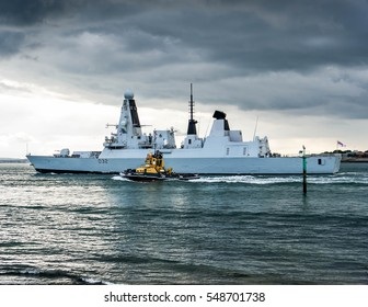 Portsmouth, England, 26th September 2012. Type 45 Destroyer HMS Daring leaves Portsmouth Harbour under heavy storm clouds accompanied by the tug SD Independent..