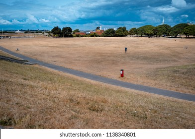 Portsmouth, England - July 18, 2018: Dry brown grass field on Southsea Common public park due to the extreme hot weather this year.