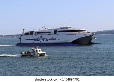 Portsmouth, Hampshire, England - July 13th 2019: High speed Brittany Ferries vessel Normandie Express seen near Portsmouth Point, Old Portsmouth with small inshore fishing boat in foreground.