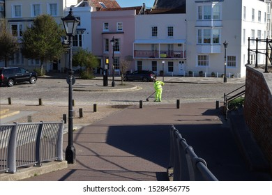 Portsmouth, Hampshire, England - October 2nd 2019: Street sweeper. Early morning at Grand Parade, Old Portsmouth. showing period historic houses and traditional style lamp post in foreground.