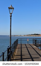 Portsmouth, Hampshire, England - October 2nd 2019: Traditional style streetlamp on deserted fishing pier at The Hotwalls, Old Portsmouth with Gosport and Isle of Wight visible on the horizon.