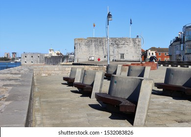 Portsmouth, Hampshire, England - October 2nd 2019: The Saluting Platform at Old Portsmouth looking along the sea wall towards The Square Tower. A popular place to sit and watch the ships go by.