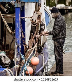 Portsmouth, Hampshire, UK 02/06/19 an old trawler fisherman adjusting fishing nets on a fishing trawler docked in a harbour