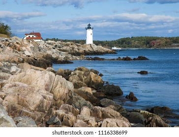 Portsmouth Harbor (Fort Constitution) lighthouse guides fishing boat along rocky coastline.