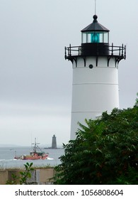 Portsmouth Harbor lighthouse in Fort Constitution guides fishing trawler with background beacon assisting in New England.