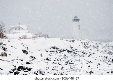 Portsmouth Harbor lighthouse in New Hampahire snowstorm with Coast Guard station nearby.