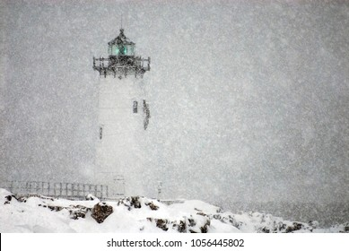 Portsmouth Harbor lighthouse, also referred to as Fort Constitution light, flashes a green light during a winter snowstorm in New Hampshire.