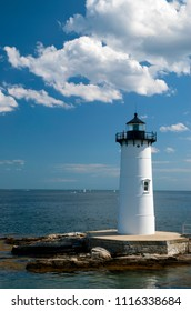 Portsmouth Harbor lighthouse, also referred to as Fort Constitution light, stands alone on a summer day with cumulus clouds passing by.