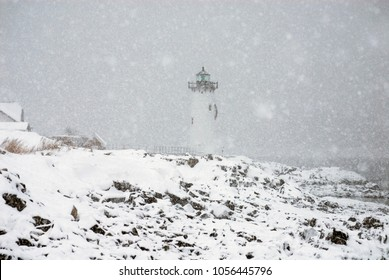 Portsmouth Harbor lighthouse shines a bright green light over the rocky shore during a snowstorm in New England.