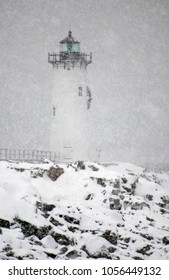Portsmouth Harbor lighthouse shines green light during snowstorm on rocky New Hampshire seacoast.