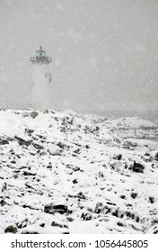 Portsmouth lighthouse, also known as Fort Constitution light, shines a green light during a New England snowstorm.