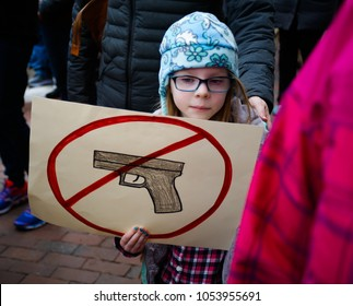 "Portsmouth, New Hampshire: March 24,2018:  A young girl holds a sing saying ""no guns"" at the March for our Lives""  rally.  School shootings don't just affect the victims. They affect everyone."