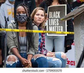 Portsmouth, New Hampshire (USA) - June 7th, 2020).  Thousands gathered at Market Square to request justice for George Floyd. Sitting girls (black and white)