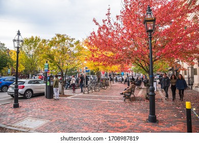 Portsmouth, NH - October 13, 2019: People enjoying a warm autumn afternoon in a small brick square along Pleasant Street in downtown. Portsmouth is a New Hampshire port city on the Piscataqua River.