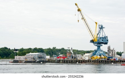 Portsmouth, NH, USA - August 2, 2014: Cranes stand at the ready at the Portsmouth Naval Shipyard on this Saturday afternoon in mid-summer.