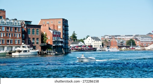 Portsmouth, NH, USA - August 9, 2014: A motorboat cruises out of Old Harbor on a sunny summer morning.