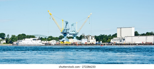 Portsmouth, NH, USA - August 9, 2014: Giant cranes stand at the ready at the Portsmouth Naval Shipyard on this sunny summer morning.