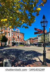Portsmouth, NH / USA - Oct 16, 2018: Street light and autumn leaves at the corner of Congress Street and Pleasant Street in Market Square. 1805 Federal style building in background is the Athenaeum.