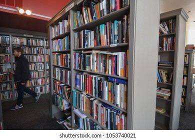 Portsmouth, N.H./USA - March 23, 2018: A customer browses aisles at Book and Bar, a combination used book store and restaurant. Bookstores have sought creative ways to stay open in the internet age.