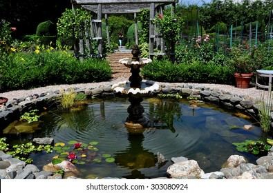 Portsmouth, Rhode Island - July 16, 2015:  Fountain and lily pad pond with perennial flowers and pergola at Green Animals Topiary Gardens