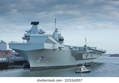 PORTSMOUTH, UK - 16 AUGUST 2017: The UK Royal Navy newest aircraft carrier HMS QUEEN ELIZABETH arrives at dawn at its new home port Portsmouth in overcast weather welcomed by enthusiastic crowds.