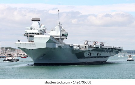 PORTSMOUTH, UK – 17TH JUN 2019: The Royal Navy aircraft carrier HMS QUEEN ELIZABETH leaving the Naval Base for five weeks of trials prior to its summer deployment to the United States