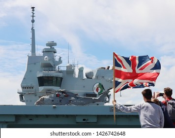 PORTSMOUTH, UK – 17TH JUN 2019: The aircraft carrier HMS QUEEN ELIZABETH passing well-wishers who had gathered to see the ship sail for 5 weeks of sea trials prior to its US deployment in the summer