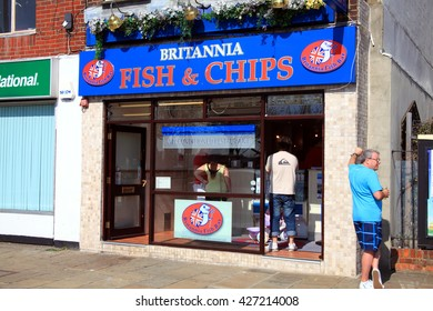 Portsmouth, UK, April 22, 2011 : Britannia Fish & Chips shop at The Hard, Portsea, serving customers in the city of Portsmouth while a male holiday maker drinks a pint of beer outside