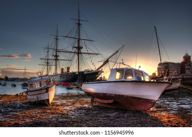 PORTSMOUTH, UK - AUGUST 10, 2018: Portsmouth harbour during sunset with small boats and HMS Warrior in the background. HDR style picture