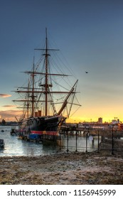 PORTSMOUTH, UK - AUGUST 10, 2018: Portsmouth harbor during sunset with small boats and HMS Warrior in the background. HDR style picture