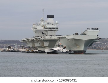 PORTSMOUTH, UK – DEC 10TH 2018: A small flotilla of tugs berth the Royal Navy aircraft carrier HMS QUEEN ELIZABETH as she returns home from trials in the Western Atlantic