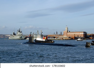 PORTSMOUTH, UK - FEB 22, 2014: USS New Hampshire SSN-778, a Virginia Class Nuclear Submarine arriving at Portsmouth Harbour.  HMS Illustrious is in the background.