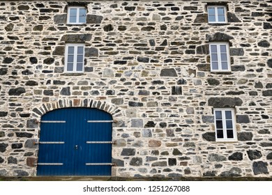 Portsoy, Aberdeenshire, Scotland, UK - June 16, 2018: Blue door and windows on stone house at Old Harbourside Portsoy Aberdeenshire Scotland UK