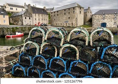 Portsoy, Aberdeenshire, Scotland, UK - June 16, 2018: Lobster traps on stone dock of Old Harbourside Portsoy with stone Portsoy Marble warehouse Aberdeenshire Scotland UK
