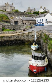 Portsoy, Aberdeenshire, Scotland, UK - June 16, 2018: Moored boats and the Shore Inn at the Old Harbour with stone buildings of Portsoy Aberdeenshire Scotland UK